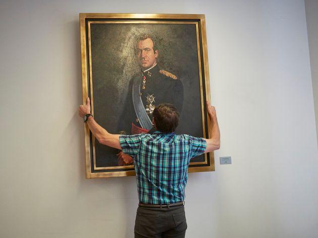 Un trabajador del Parlamento de Navarra retira el retrato del rey Juan