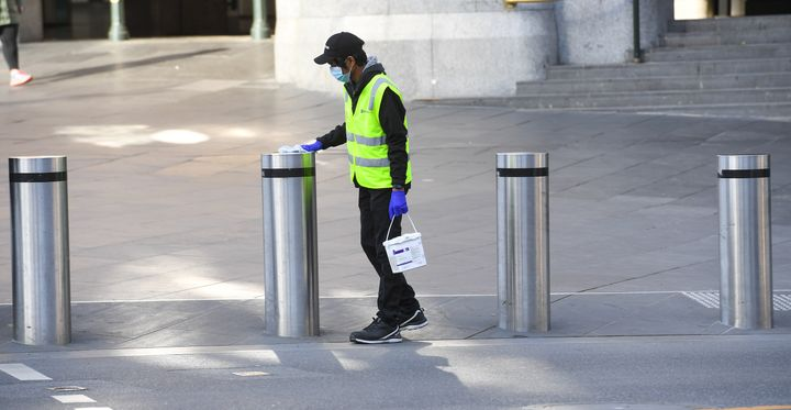 A worker cleans posts in Melbourne on Aug. 3, 2020 after the state announced new restrictions as the city battles new outbreaks of COVID-19.