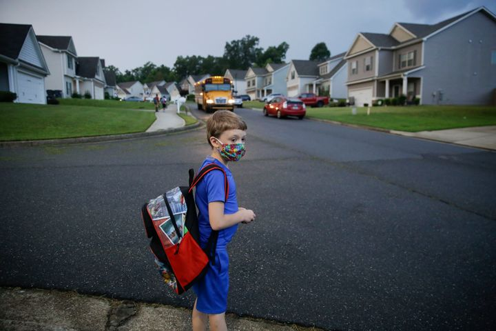 A 7-year-old boy wearing a mask waits at the bus stop on Aug. 3, the first day of school in Dallas, Georgia.