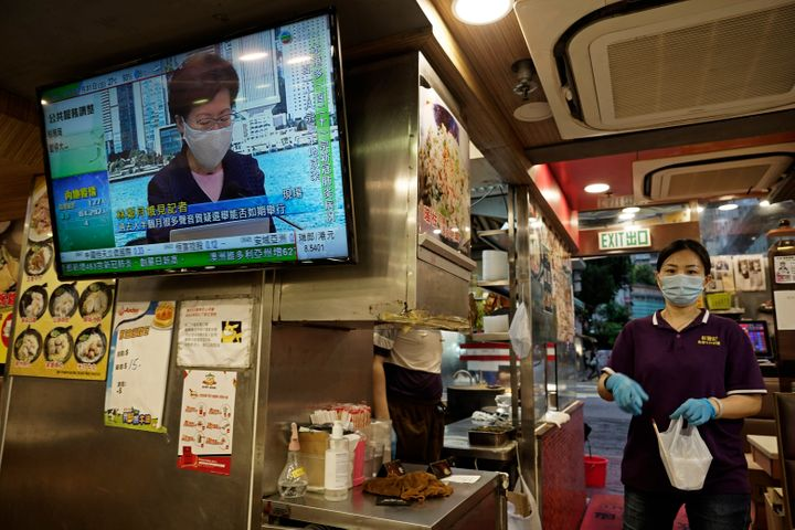 A restaurant employee prepares a takeaway meal while a TV screen shows Hong Kong Chief Executive Carrie Lam during a news conference in Hong Kong on July 31, 2020.