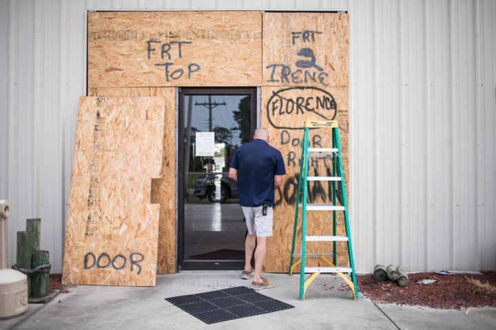 Terry Crabtree finishes boarding up the entrance to Downeast Marine in Otway, N.C. as Tropical Storm Isaias approaches on Mon
