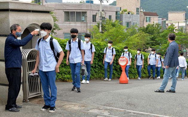 (자료사진) 울산의 한 고등학교에서 학생들이 교문 앞에서 발열체크를 받고 있다. 2020년