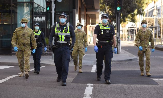 A group of police and soldiers patrol the Docklands area of Melbourne on August 2, 2020, after the announcement...