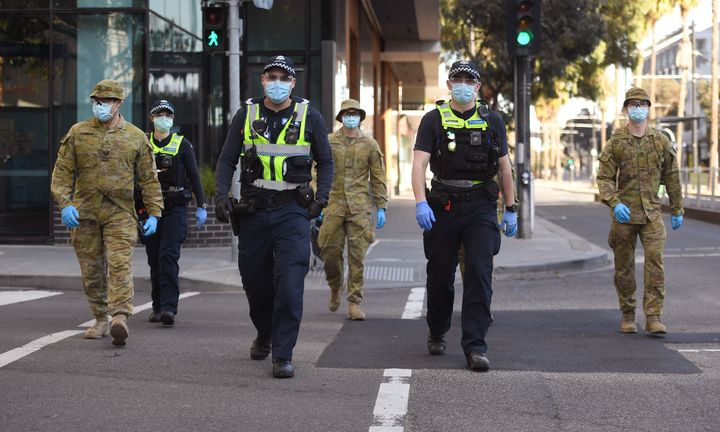 A group of police and soldiers patrol the Docklands area of Melbourne on August 2, 2020, after the announcement of new restrictions to curb the spread of the COVID-19 coronavirus.