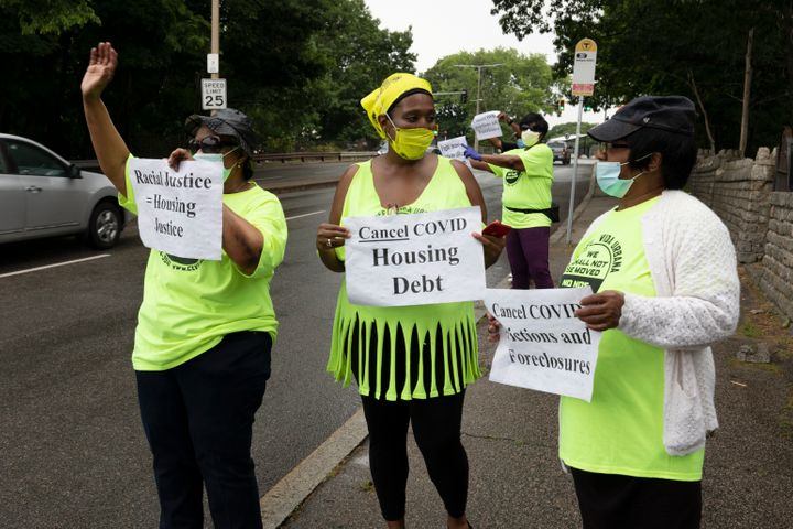 Annie Gordon, left, Gabrielle Rene, center, and Jenny Clark, right, rally for protection from evictions on June 27, 2020, in