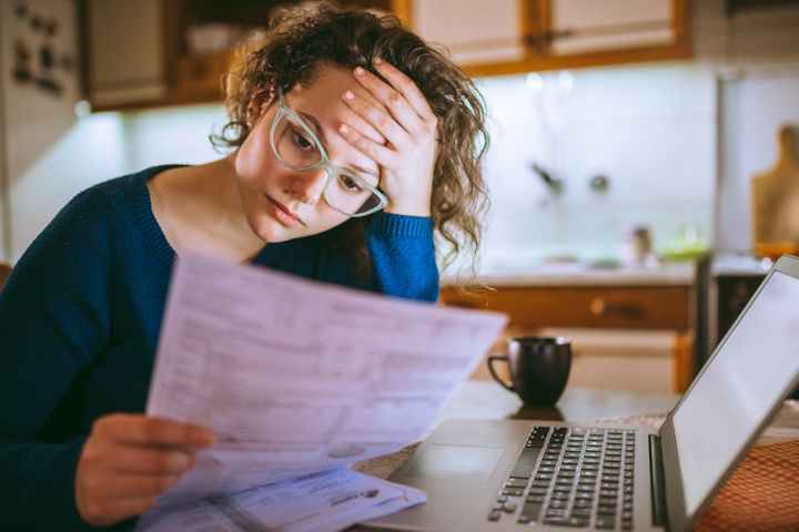 A woman reads over her credit card statements in this stock photo. A credit score above 680 is considered good for your financial health.