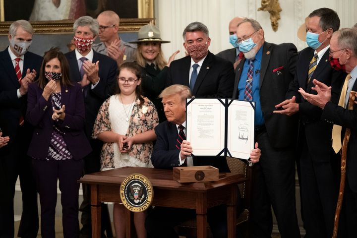 President Donald Trump signs the Great American Outdoors Act during a singing ceremony in the East Room of the White House on
