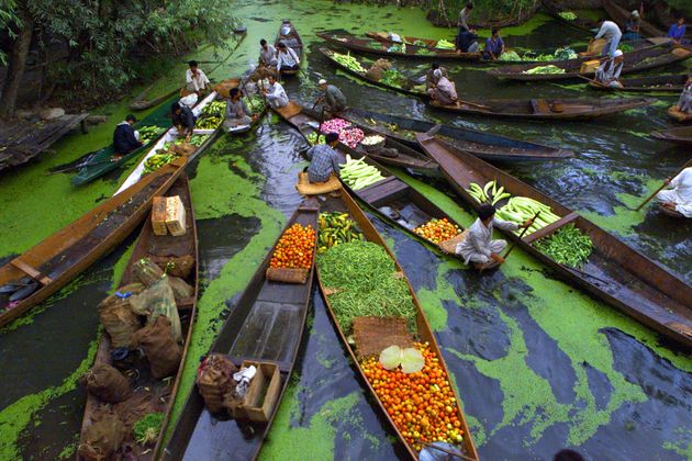 Kashmiri vegetable sellers gather at a floating market on Dal Lake in Srinagar, the summer capital of...