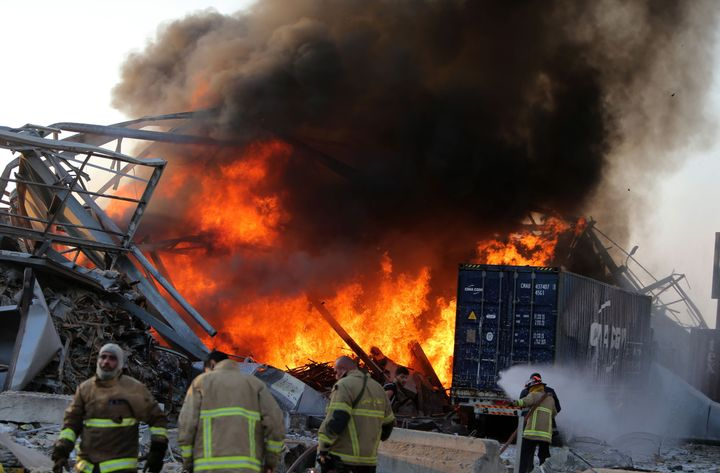 Lebanese firefighters extinguish fire at the scene of an explosion at the port in the capital Beirut.