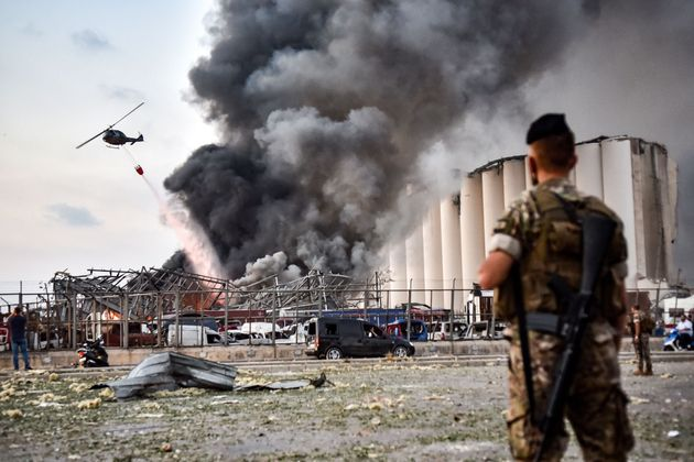 EDITORS NOTE: Graphic content / Lebanese army soldiers stand while behind a helicopter puts out a fire...