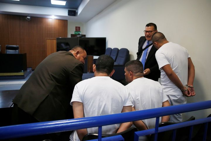 Three former El Salvador police officers, seen here conferring with their lawyers during their trial, were found guilty in la