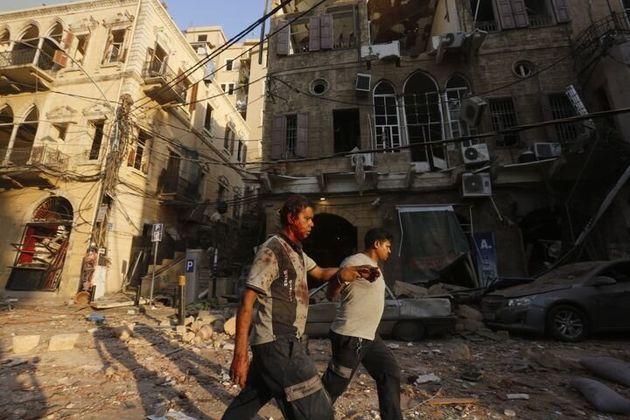 怪我をした男性が、助けを借りながら瓦礫の中を歩く
