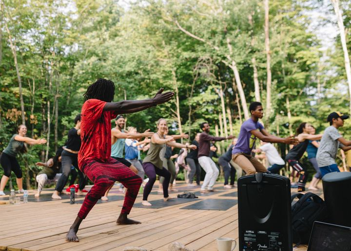 Emmanuel Jal, seen pre-pandemic, leading participants in a guided dance and yoga session.
