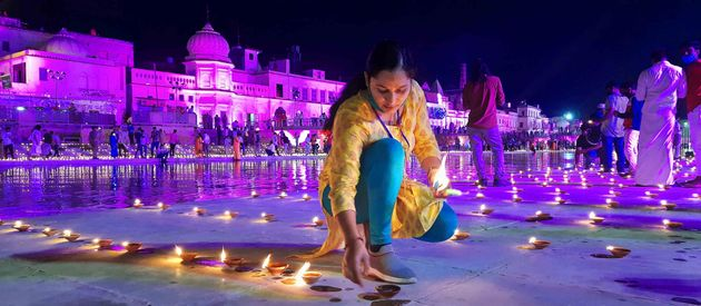 A woman in Ayodhya lights lamps on the eve of the Ram Mandir 'Bhoomi Pujan' on August 4,
