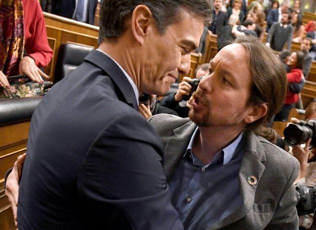 Pedro Sánchez y Pablo Iglesias se abrazan tras la investidura del primero como presidente del...
