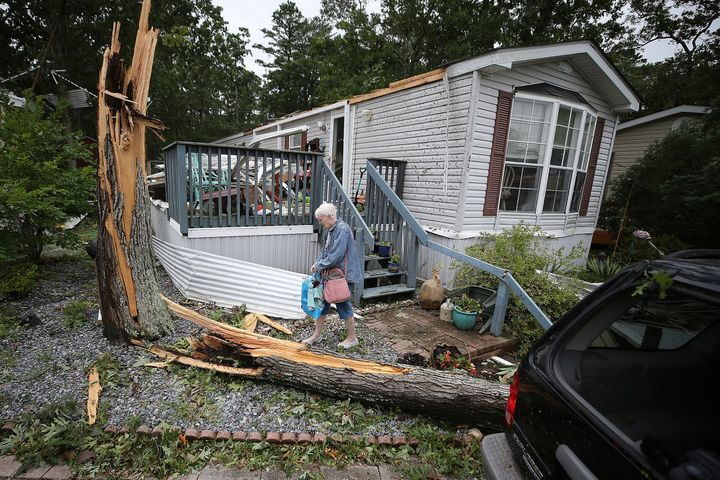 Ellen Mallen, who lives in a mobile home court, carefully leaves her home after a suspected tornado spawned by Isaias struck