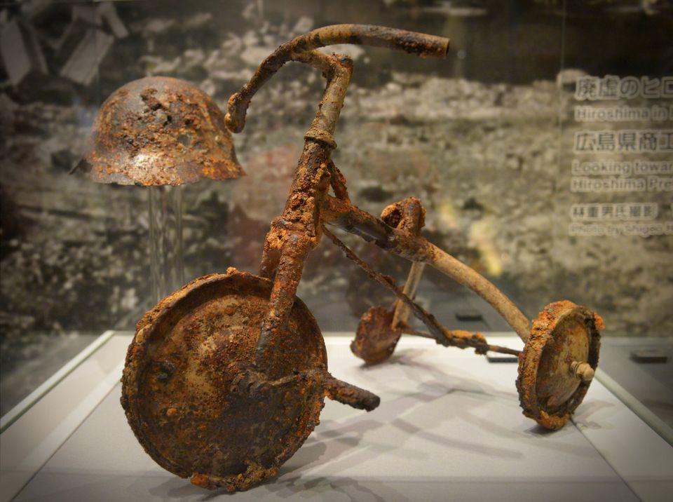 Um triciclo e um capacete incinerados estão expostos no Museu da Paz em