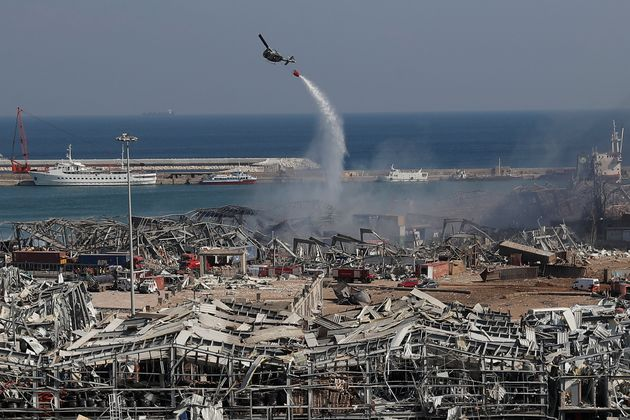 An army helicopter drops water at the scene of Tuesday's massive explosion that hit the seaport of Beirut,...