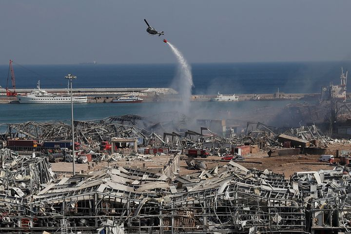 An army helicopter drops water at the scene of Tuesday's massive explosion that hit the seaport of Beirut, Lebanon, Wednesday