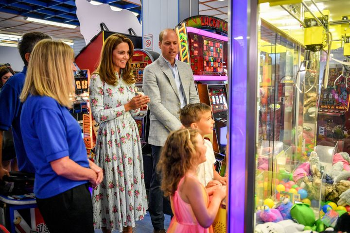 Kate and William watch children play a grab a teddy game at Island Leisure Amusement Arcade during their visit to Barry Islan