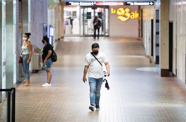 People wear face masks as they walk through a tunnel in a metro station in Montreal on