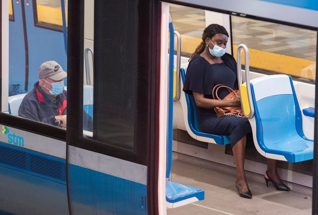 People wear face masks as they commute via metro in Montreal on