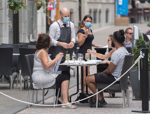 Servers wear face masks as they take orders at an outdoor terrace in Montreal on July 26,