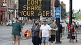A sign encouraging the wearing of masks and keeping social distancing stands at a street corner Wednesday, Aug. 5, 2020, in downtown Nashville, Tenn. The wearing of face coverings is required in most public indoor and outdoor situations in Nashville due to an increase of COVID-19 cases. (AP Photo/Mark Humphrey)