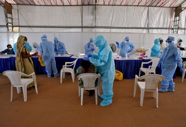A healthcare worker wearing protective gear takes a swab from a woman for a rapid antigen test, amidst...