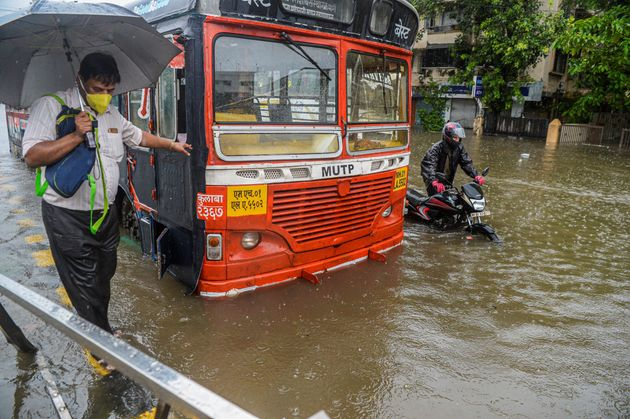 Commuters make their way through a flooded road in Mumbai on August 4,