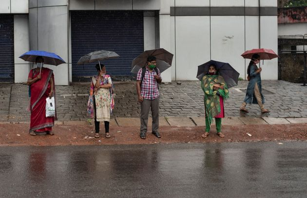 People stand holding umbrellas during monsoon rains amid the coronavirus pandemic in Kochi, June 6,