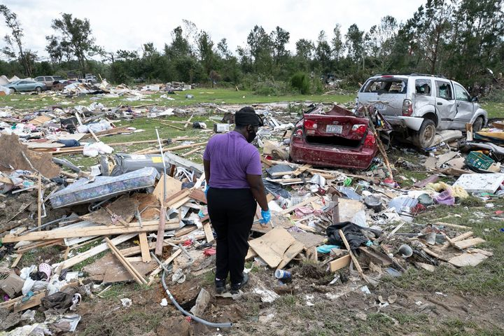 Cynthia Cooper looks for personal items for a family member who had their home destroyed after a tornado spawned by Hurricane
