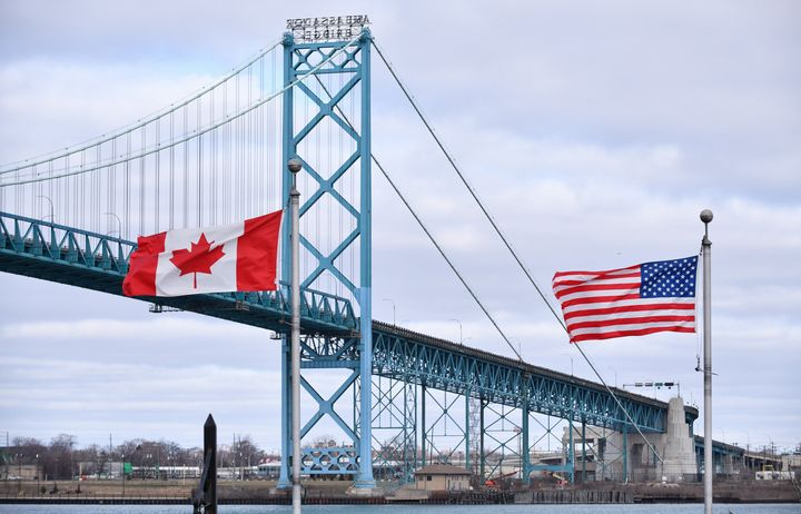 Canadian and American flags fly near the Ambassador Bridge at the Canada-U.S. border crossing in Windsor, Ont. on March 21, 2020. country.