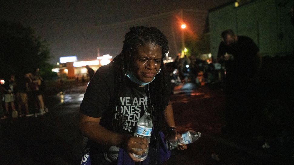 Cori Bush uses water to rinse her face after being tear-gassed by police in Florissant, Missouri, on July 5. She went back to