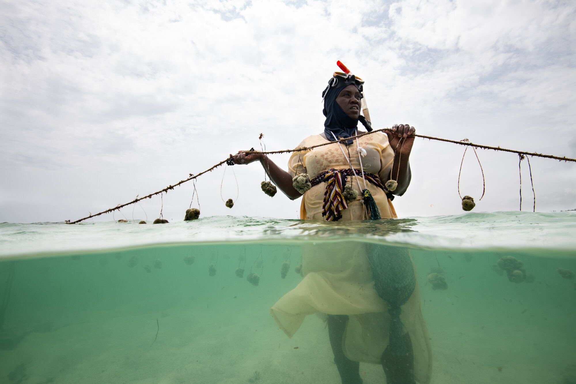 Nasir Hassan Haji holds a rope of sponges on her farm. She was one of the first 2 sponge farmers in Jambiani and previously f