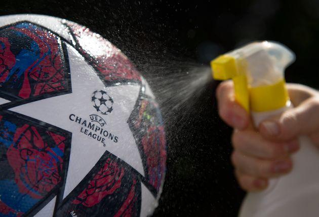 Un operario rocía con desinfectante el balón oficial de la Champions, una imagen que se...