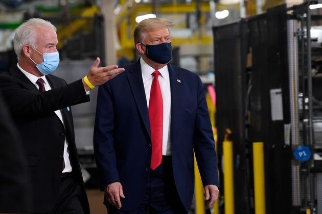 U.S. President Donald Trump wears a mask as he gets a tour from Whirlpool's Jim Keppler during a tour...