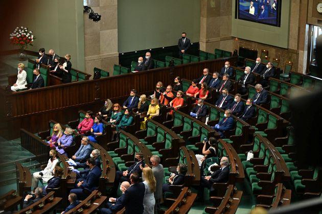 Parlamentares sentam em fileira para formar bandeira LGBT nas cadeiras do parlamento polonês, em