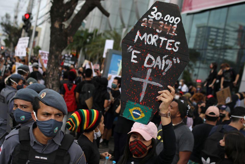 Em protesto contra a violência policial realizado durante a pandemia, manifestante segura cartaz...