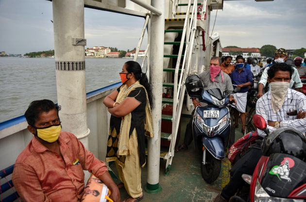 People wearing masks travel in a ferry during the coronavirus pandemic in Kochi, May 29,