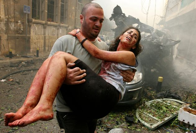 A wounded woman is carried at the site of an explosion in Ashrafieh, central Beirut, October 19, 2012....