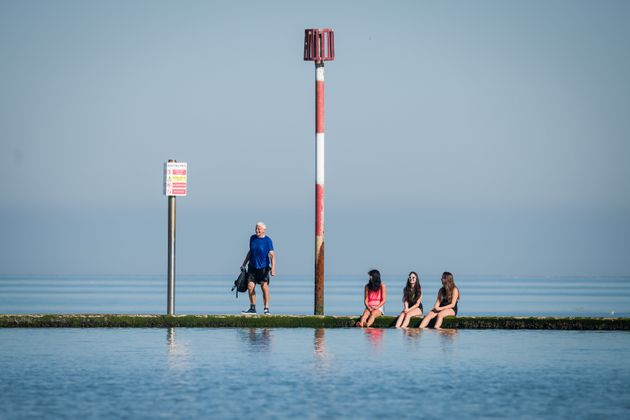 A man talks to three girls as they dip their feet in the saltwater lido on Friday in