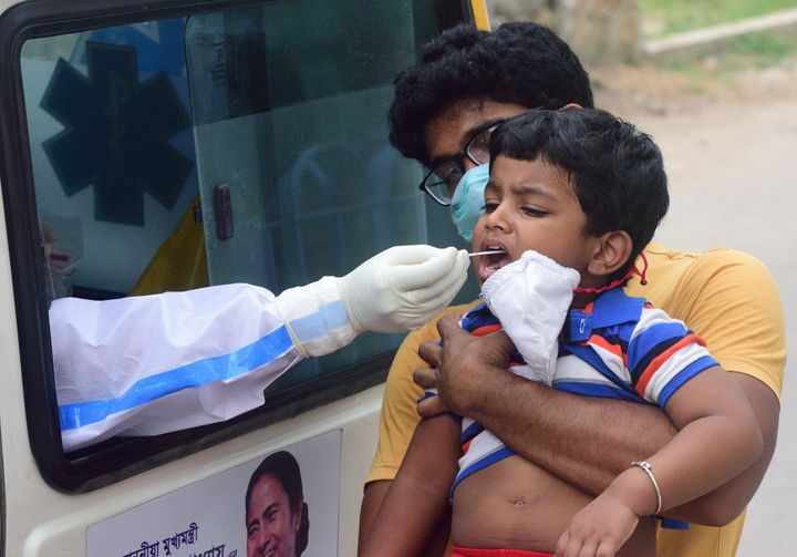 Officials of the Kolkata Municipal Corporation health department conduct a test on a boy in Kolkata on August 7, 2020.