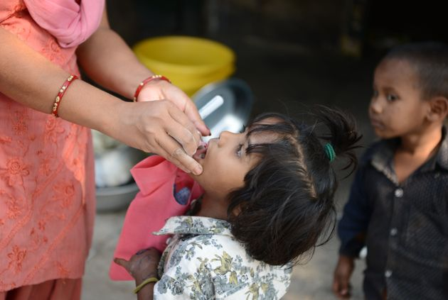 An child receives polio drops from a health worker during a polio immunisation programme in Siliguri...