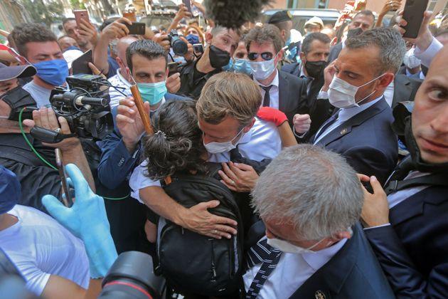 Une jeune Libanaise étreint le président Emmanuel Macron lors d'une visite dans le quartier...