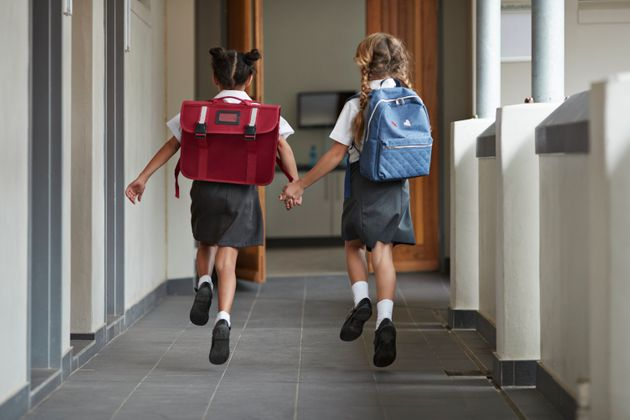 Two young students run in a school hallway in this undated stock photo. Masks are not mandatory for children...