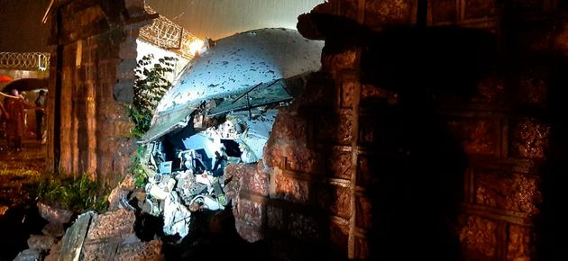 A part of the Air India Express flight is seen through a broken wall after it skidded off a runway while...