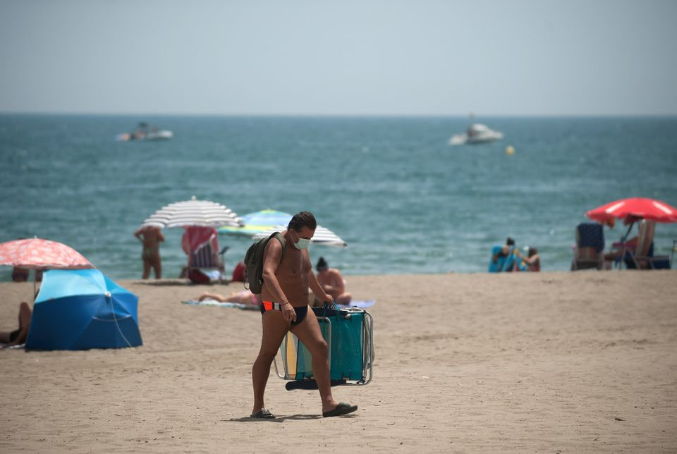 A man wearing a face mask carrying chairs at Rincon Sol beach of Torremolinos in Malaga during a hot...