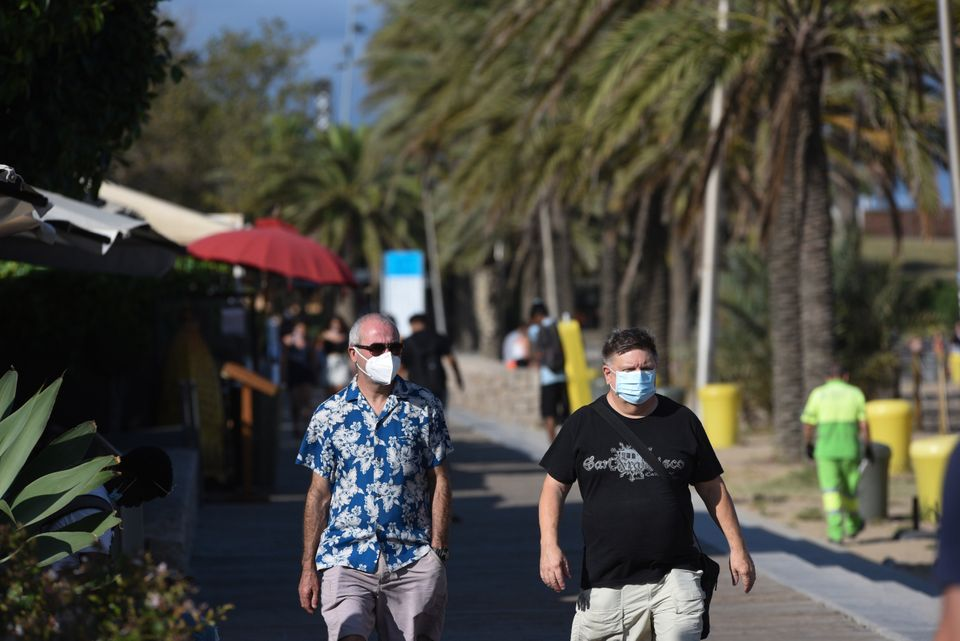 Tourists wearing face masks as a preventive measure walk along Somorrostro beach during the coronavirus
