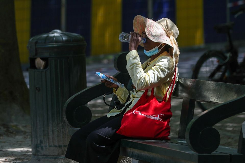 A woman drinks water as she sits on a bench during a heatwave, in Brussels,